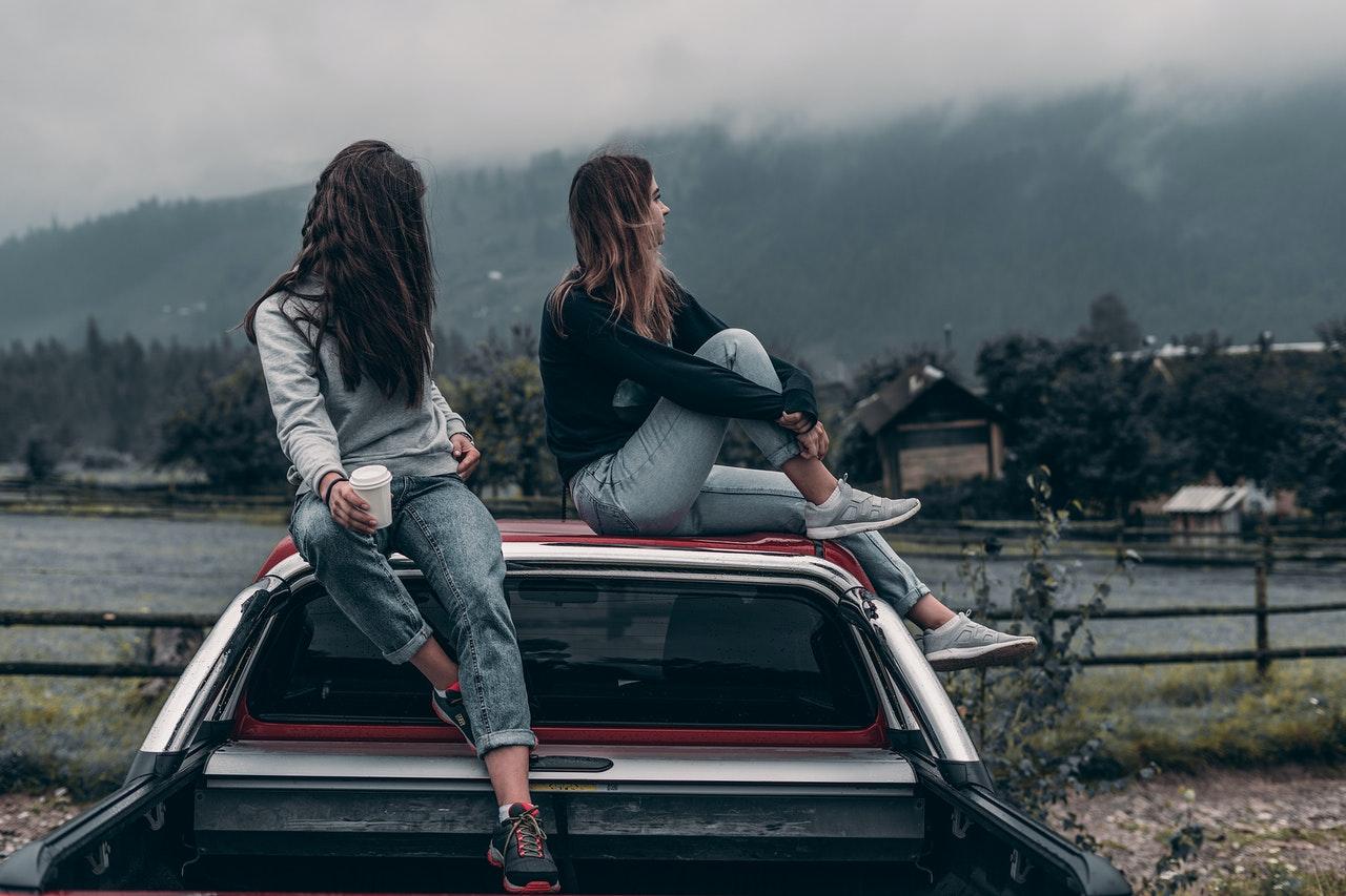 dziewczyny siędziące na dachu auta
